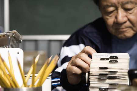 Senior Asian man looking at circular card file
