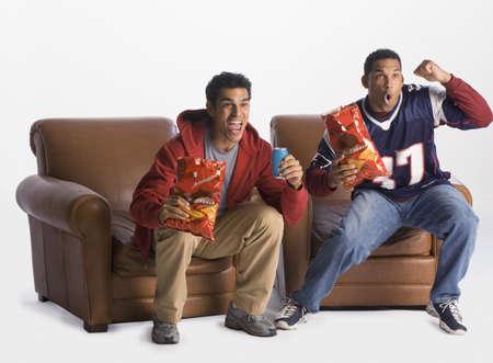 Multi-ethnic men cheering in armchairs