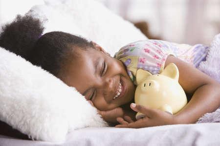 African American girl hugging piggybank