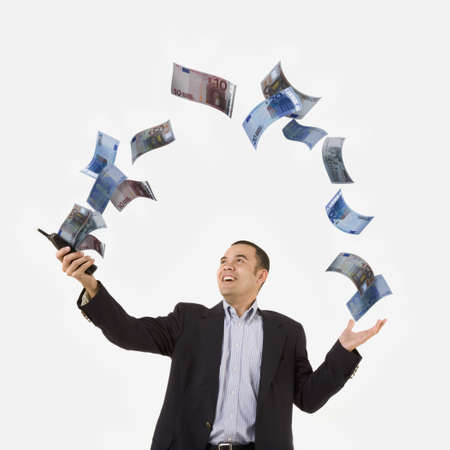 Money flying out of telephone in Asian businessman's hand LANG_EVOIMAGES