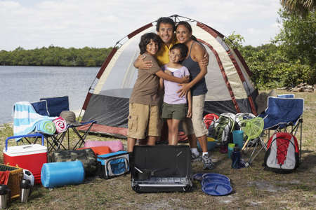 Hispanic family surrounded by camping supplies