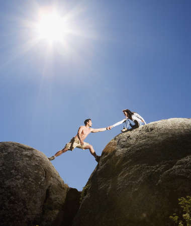 Multi-ethnic couple climbing rock formations