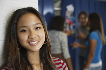 Asian teenaged girl in front of school lockers LANG_EVOIMAGES