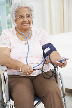 Senior African American woman taking own blood pressure LANG_EVOIMAGES