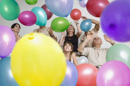 Multi-generational Hispanic family surrounded by balloons LANG_EVOIMAGES