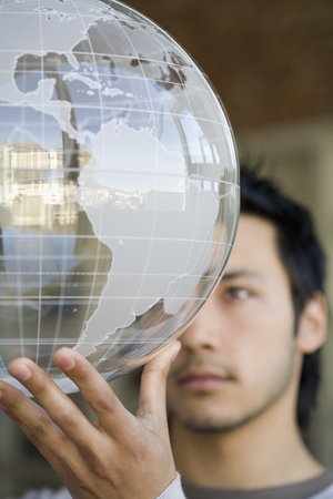 Asian man holding globe LANG_EVOIMAGES