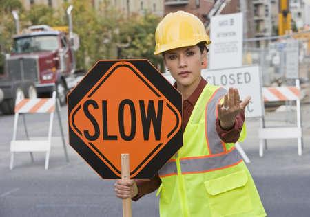 Hispanic female construction worker holding slow sign
