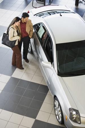 Hispanic couple looking at new car