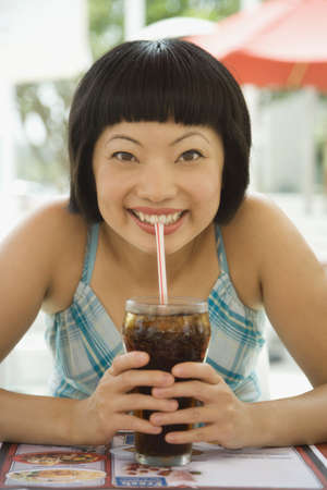 Asian woman drinking soda with straw