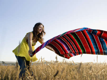 Hispanic woman laying blanket in field LANG_EVOIMAGES
