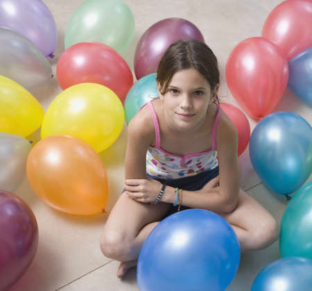 Hispanic girl on floor with balloons LANG_EVOIMAGES