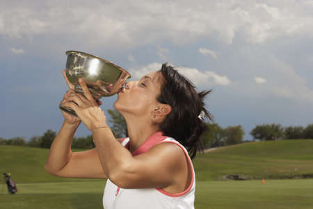 Hispanic woman kissing golf trophy