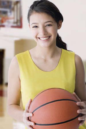 Hispanic teenaged girl holding basketball LANG_EVOIMAGES