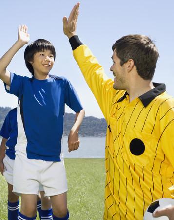 Asian boy high-fiving soccer coach