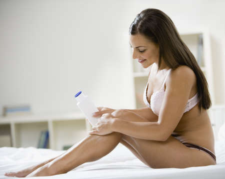 Woman in underwear applying lotion