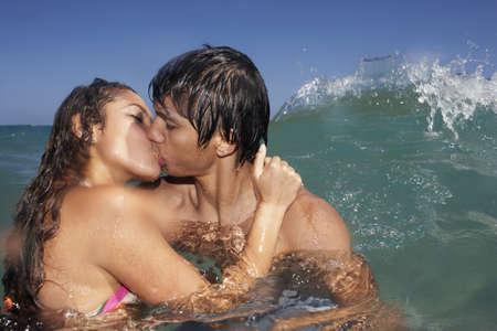 Hispanic couple kissing in ocean