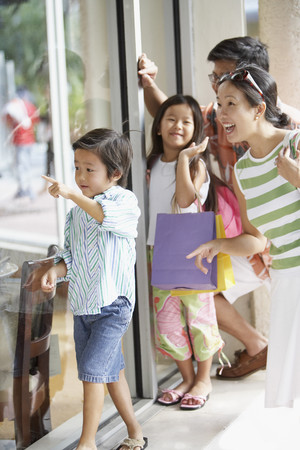 Asian family window shopping LANG_EVOIMAGES