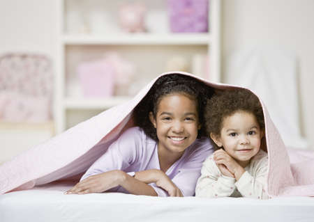 African sisters laying under blanket