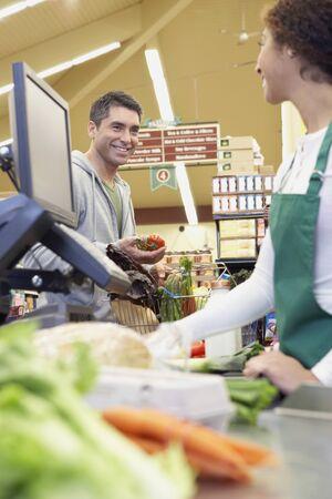 Hombre hispano mirando en la tienda de comestibles