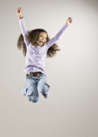 Mixed Race girl jumping in air LANG_EVOIMAGES
