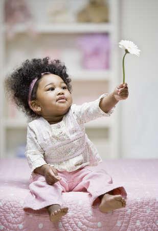 African baby girl holding flower
