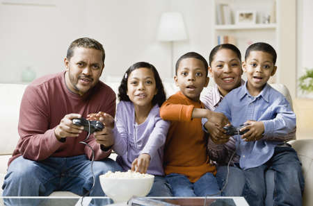 Mixed Race family playing video games LANG_EVOIMAGES