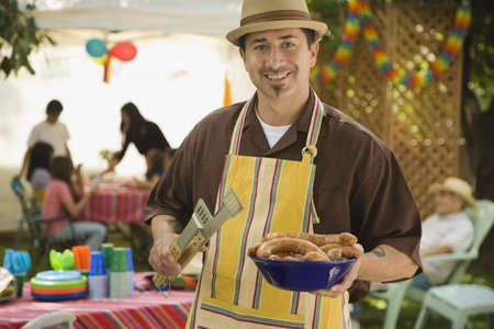 Hispanic man holding food at barbecue LANG_EVOIMAGES