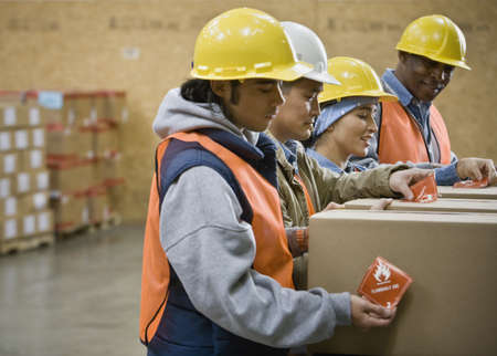 Multi-ethnic warehouse workers applying warning stickers to packages