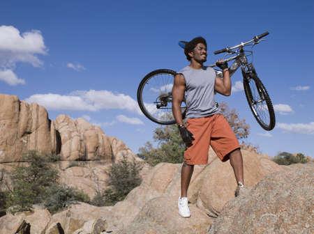 African man holding mountain bike on rocks LANG_EVOIMAGES