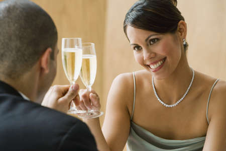 Hispanic couple toasting with champagne LANG_EVOIMAGES