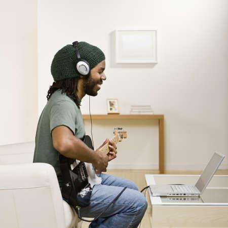 African man playing guitar LANG_EVOIMAGES