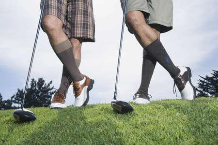 Multi-ethnic men on golf course LANG_EVOIMAGES
