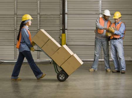 Hispanic warehouse worker pushing boxes on hand truck