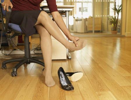 Indian businesswoman rubbing foot