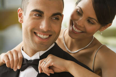 Mixed Race woman adjusting husband's bowtie LANG_EVOIMAGES