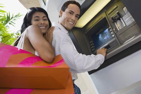 Hispanic couple using atm