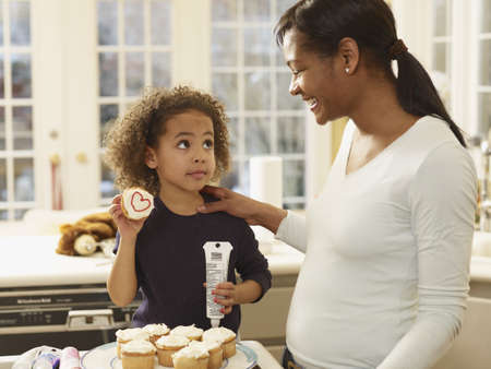 African mother and daughter decorating cupcakes LANG_EVOIMAGES