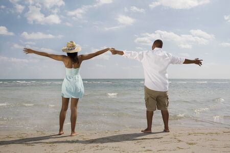 African couple with arms outstretched at beach