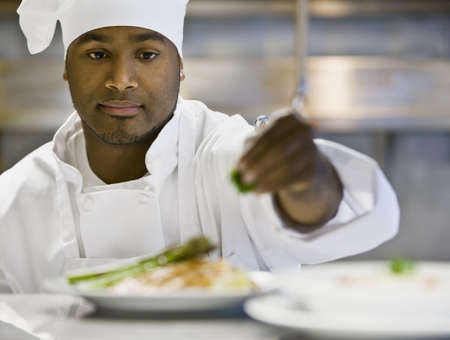 African male chef garnishing plate of food