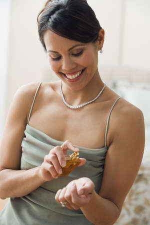 Mixed Race woman putting on perfume LANG_EVOIMAGES
