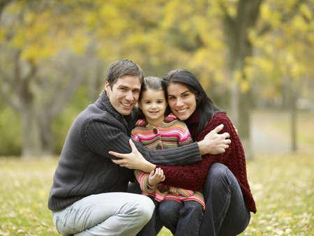 Multi-ethnic family hugging in park LANG_EVOIMAGES