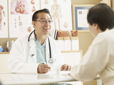 Senior Asian male doctor talking to patient