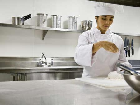 Asian female chef sprinkling flour on dough LANG_EVOIMAGES