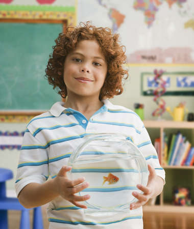 Mixed Race boy holding fish bowl LANG_EVOIMAGES
