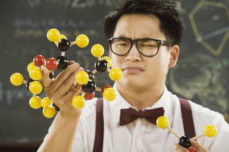 Nerdy Asian male student holding molecular model LANG_EVOIMAGES