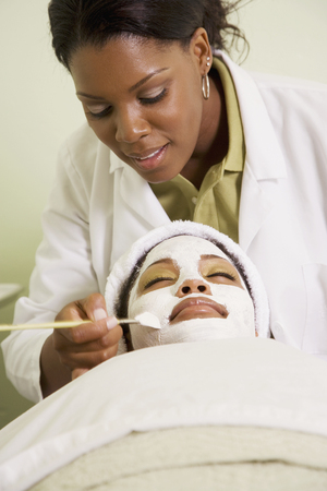 African woman receiving spa facial treatment LANG_EVOIMAGES