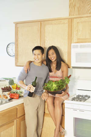 Asian couple with food and wine in kitchen