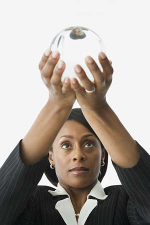 African businesswoman holding up crystal ball