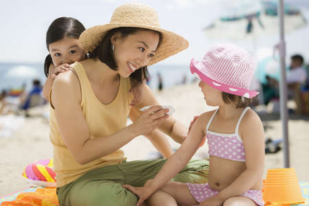 Asian mother applying sunscreen to daughter LANG_EVOIMAGES