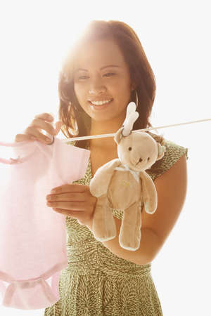 Asian woman hanging baby clothing on clothes line LANG_EVOIMAGES